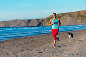 Fitness woman and dog running on beach — Stock Photo
