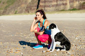 Fitness woman and dog on beach — Photo