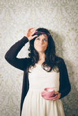 Pensive and suspecting woman on retro wall with coffee — Stok fotoğraf