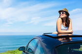Woman on summer vacation leaning out sunroof — Stock Photo