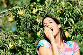 Female farmer eating fruit from pear tree — Stock Photo