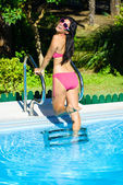 Joyful woman having fun at swimming pool on summer — ストック写真