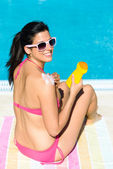 Woman on summer vacation sunbathing with suntan lotion — Stockfoto