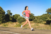 Sporty fit woman running in country road — Stock Photo