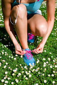 Woman lacing running shoes in spring — Stock Photo