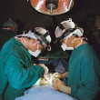 Stock Photo: Two surgeons operating