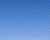 冷凝水在玻璃上形成了在一个蓝色的背景 — 图库照片