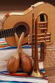 accoustic guitar, maracas and trumpet on mexican fabric — Stock Photo