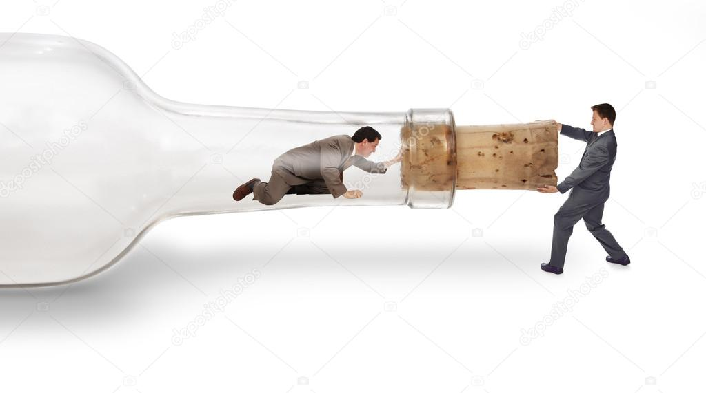 A businessman trapped inside a bottle trying to crawl out through the neck with his partner pulling on the cork from the outside — Stock Photo #13482353