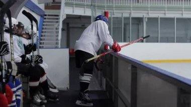 Hockey player closes the door behind him and sits on the bench — ストックビデオ