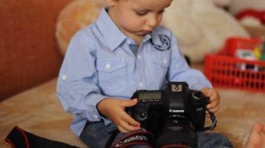 Kleine junge in ein blaues hemd untersucht die kamera — Stockvideo