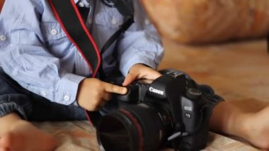 Kind in einem jeans-kleid drückt den auslöser der kamera — Stockvideo