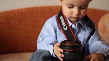 Niño en un vestido de mezclilla explora la lente de la cámara — Vídeo de stock