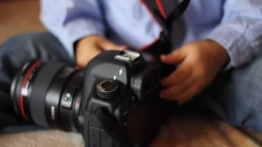 Child examines a professional camera — Stock video