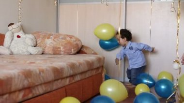 Little boy enthusiasm kicks colorful balloons at home — Stock Video