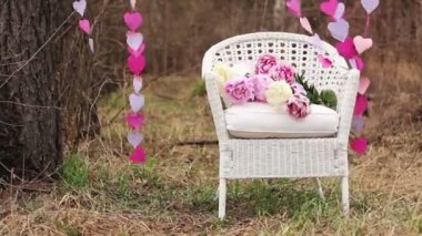 Decorations for an artistic photo-shoot: White Chair and a garland of paper hearts — Stock Video