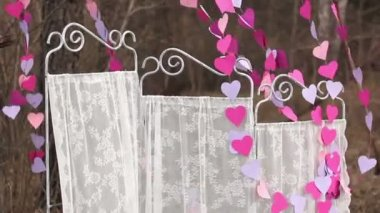 Decorations for an artistic photo-shoot: White screen and a garland of paper hearts — Stock Video