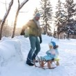 Stock Video: Young father sledding his child in winter park