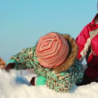 Stock Video: Young mother plays in snow drift with her child