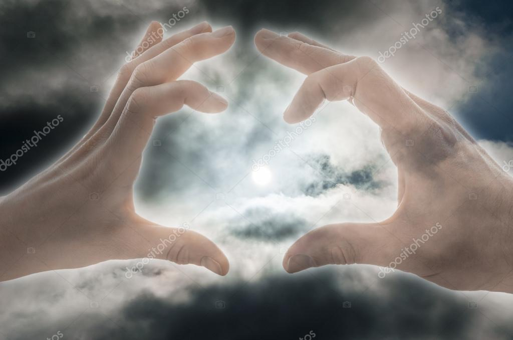 Female and male hand making a heart shape with sun in the center and cloudy sky in background. — Stock Photo #19274717