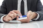 Işadamı manifatura bir cep telefonu — Stok fotoğraf
