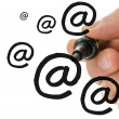 Male hand writing multiple email symbols on a virtual white boar — Stock Photo