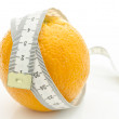 Orange with measuring tape wrapped around it — Stock Photo #23823713