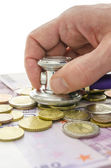 Detail of male hand checking money with stethoscope — Stock Photo