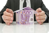 Male hands around money house — Stockfoto