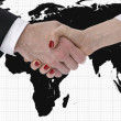 Handshake with map of the world in background — Stock Photo