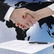 Shaking hands over map of the world — Stock Photo