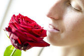 Detail of woman smelling a rose — Stok fotoğraf