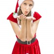 Woman in a Christmas dress blowing a kiss at you — Stock Photo
