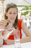Young woman pouring water into a glass — Stock Photo