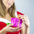 Miss santa oppening a present — Stock Photo
