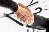 Business handshake over white clock — Stock Photo