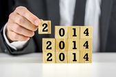 Businessman with 2014 New Year building blocks — Stock Photo