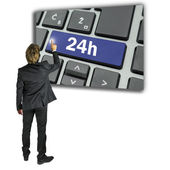 Businessman activating a 24h key on a keyboard — Stock Photo