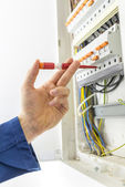 Electrician checking the electrical supply box — Stock Photo