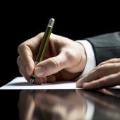 Businessman writing on a sheet of white paper — Stock Photo