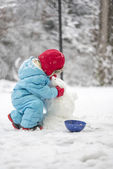 Young child building a snowman — Stock Photo