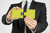 Man holding two pieces of a yellow puzzle — Stock Photo