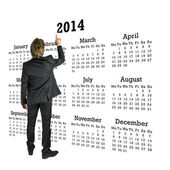 Businessman standing in front of a 2014 calendar — Stock Photo