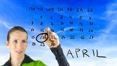 Woman marking Earth Day on a calendar — Zdjęcie stockowe