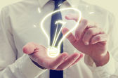Businessman with creative light bulb icon — Stock Photo
