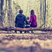 Young family sitting on a tree trunk — Stock Photo