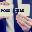 Man holding puzzle pieces with the word Possible — Stock Photo