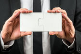 Businessman holding two puzzle pieces — Stock Photo