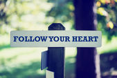 Old rustic signpost with Follow your heart sign — Stock Photo