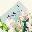 Bunch of white tiger lillies with a Miss u card — Stock Photo